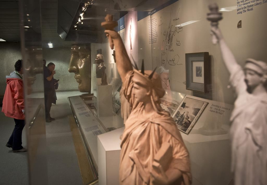 Visitors review exhibits at the Statue of Liberty museum. ( AP Photo/Bebeto Matthews)