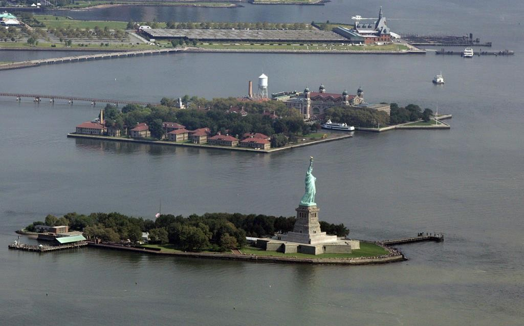 The Statue of Liberty on Liberty Island, bottom, is seen near Ellis Island, middle, and the historic Central Railroad of New Jersey Terminal, top, which a report suggests may host a low-rise hotel or an amusement park. (AP Photo/Mel Evans)