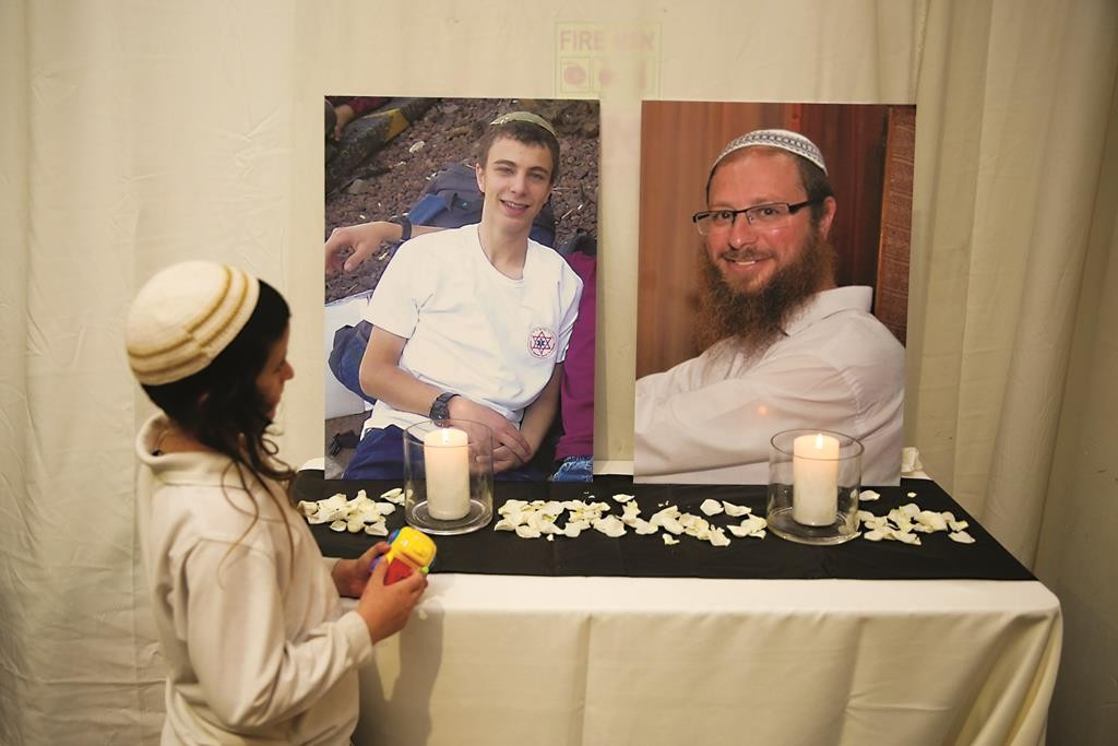 "Photos of Rabbi Yaakov Litman, Hy""d, and Netanel Litman, Hy""d, the father and brother of, ybl""c, Sarah Litman, displayed at her chasunah on Thursday night in Binyanei Ha'Uma in Yerushalayim. (Hadas Parush/Flash90)"