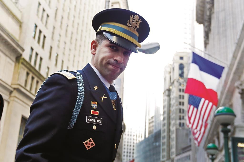 U.S. Army Capt. Flo Groberg, who was born in Paris and last week was awarded the Medal of Honor, arrives Monday at the New York Stock Exchange to ring the opening bell and lead a minute of silence in memory of the victims of the Paris attacks. (AP Photo/Richard Drew)