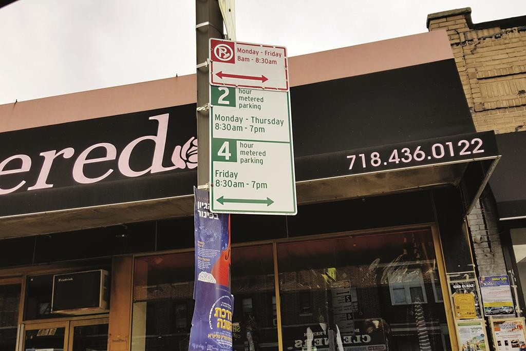 A sign hangs on Sunday morning on Boro Park's 18th Ave. and 47th Street announcing a new four-hour limit on feeding the parking meters on Erev Shabbos. (Yisroel Werdyger/Hamodia Photo)