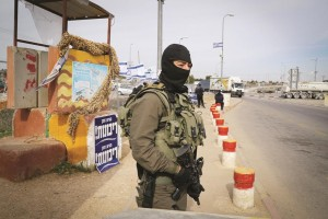 A masked Israeli special forces soldier stands guard near the Gush Etzion junction, Wednesday. (Gershon Elinson/FLASH90)