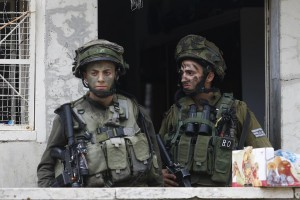 Israeli soldiers standing guard outside a Palestinian house during a search near Tel Rumeida in Chevron, on Shabbos. Three assaults took place Friday in the city. (AP Photo/Nasser Shiyoukhi)