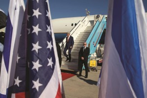 Seen through U.S. and Israeli flags, Secretary of State John Kerry walks down the stairs of his plane, Tuesday, upon arrival in Tel Aviv. (AP Photo/Jacquelyn Martin, Pool)