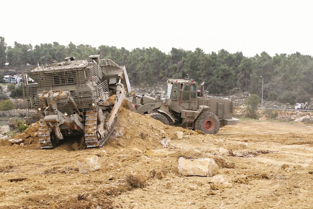 Israeli army bulldozers work to open a new road that will separate Jewish and Palestinian cars at the Gush Etzion junction, Thursday. (Gershon Elinson/Flash90)