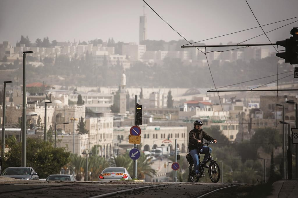 A cyclist crosses the light rail tracks over the view of northeast Yerushalayim during Wednesday's dust storm. (Hadas Parush/FLASH90)