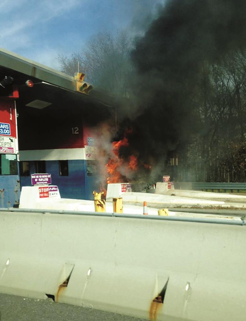 Flames rise Friday from a vehicle after it crashed into a toll plaza on the Atlantic City Expressway in Egg Harbor Township, N.J. (AP Photo)