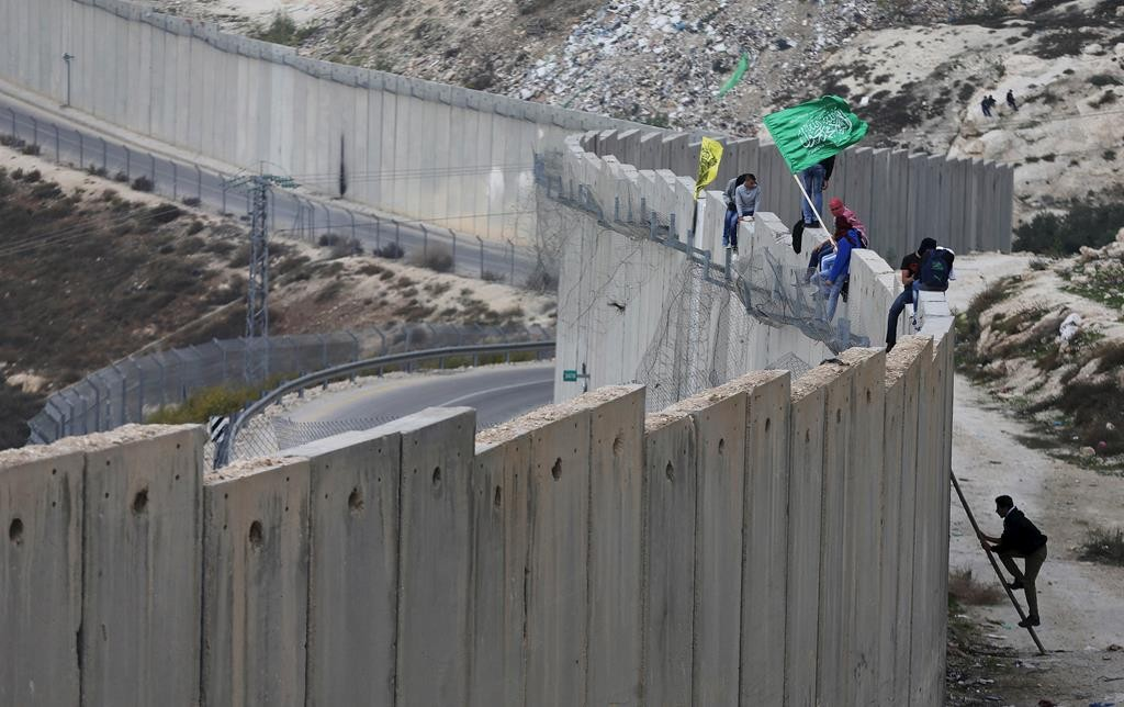 Palestinians climbing over a section of the Israeli security barrier that separates the town of Abu Dis from Yerushalayim, during disturbances on Monday. (REUTERS/Ammar Awad)