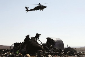 An Egyptian military helicopter flies over debris from a Russian airliner which crashed at the Hassana area in Arish city, north Egypt. (REUTERS/Mohamed Abd El Ghany)