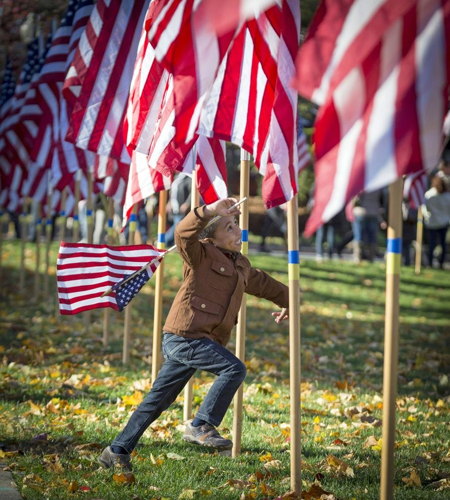 Gabriel White, four, runs among the flags Sunday during the Clifton Veterans Day Parade in Clifton, NJ. (Jim Anness/The Record via AP)
