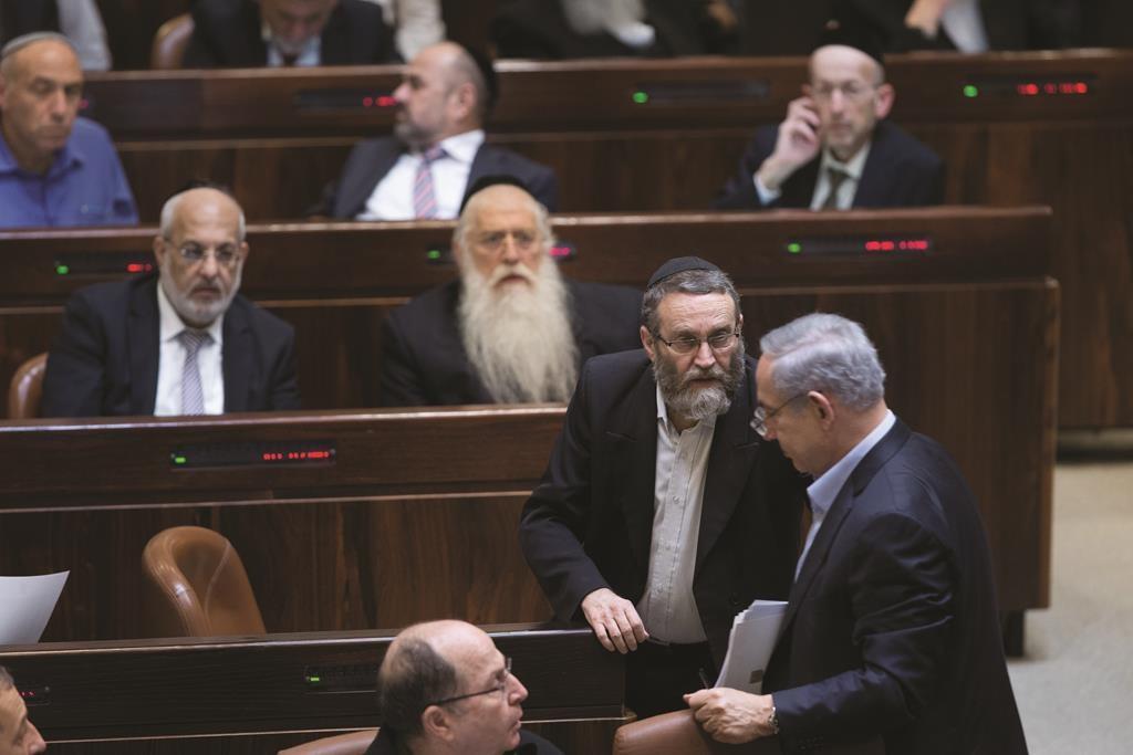 United Torah Judaism MK Rabbi Moshe Gafni speaking to Prime Minister Binyamin Netanyahu after the vote on changes in the draft law Monday night. (Yonatan Sindel/Flash90)