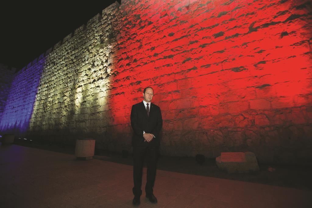 Jerusalem mayor Nir Barkat stands next to the walls of Jerusalem's Old City as they lit in red, white and blue, resembling the colours of the French flag on November 15, 2015, in solidarity with Paris, and in tribute of the victims killed in last night's terror attacks in Paris, France. Photo by Yonatan Sindel/Flash90 *** Local Caption *** ðéø áø÷ú èøåø çåîåú äòéø äòúé÷ä éøåùìéí òéø äòúé÷ä çåîåú àåø ãâì öøôú àãåí ëçåì ìáï âì èøåø ôøéæ