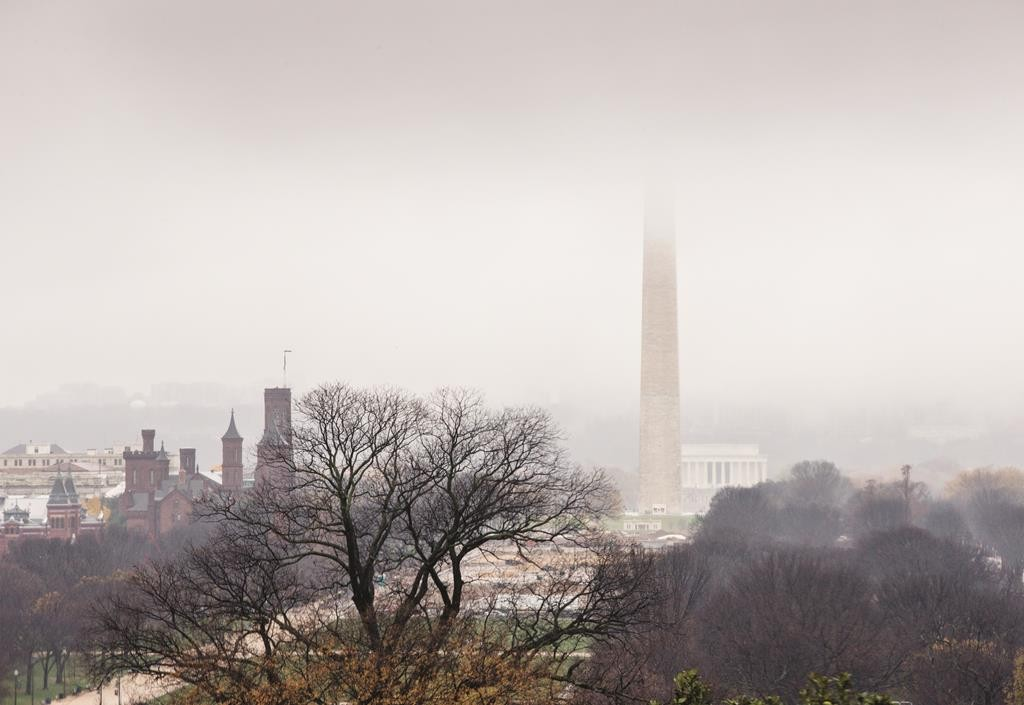 Low cloud shrouds the top of the Washington Monument, looking toward the Lincoln Memorial, as seen from Capitol Hill in Washington, Tuesday. The Smithsonian Castle is visible at left. (AP Photo/J. Scott Applewhite)