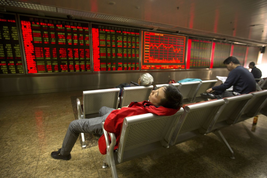 A Chinese investor naps while monitoring stock prices at a brokerage house in Beijing, Friday, Dec. 4. (AP Photo/Mark Schiefelbein)