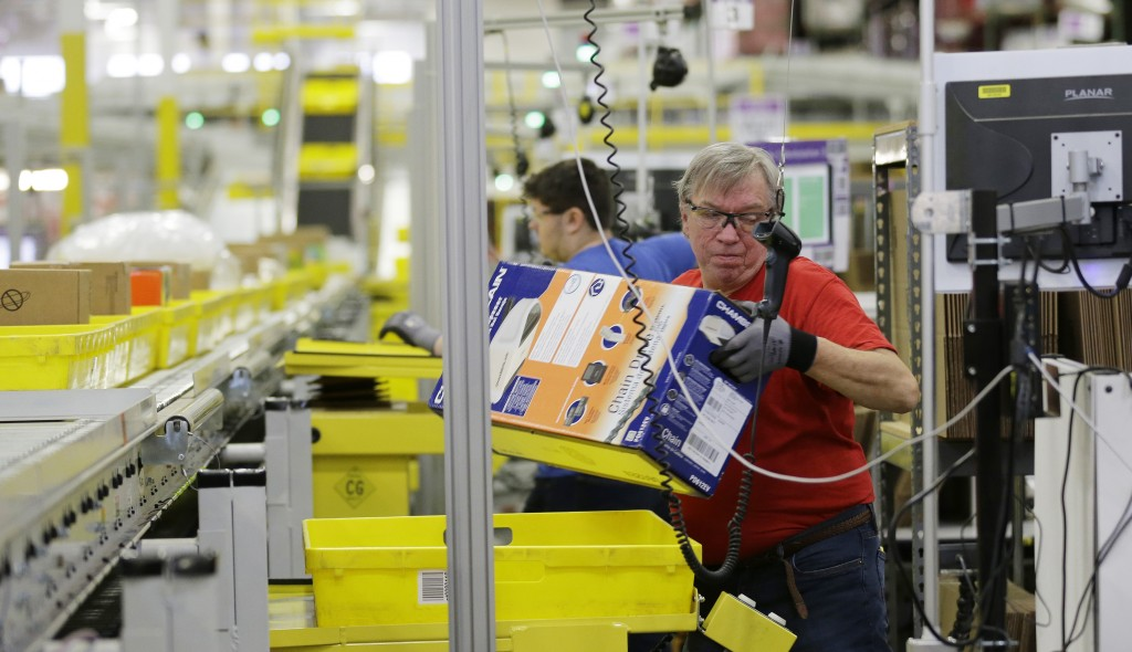 """In this Monday, Nov. 30, photo, Mark Oldenburg processes outgoing orders at Amazon.com's fulfillment center in DuPont, Wash. Shoppers spent more than $3 billion online this """"Cyber Monday,"""" making it the biggest online shopping day ever.  (AP Photo/Ted S. Warren, File)"""
