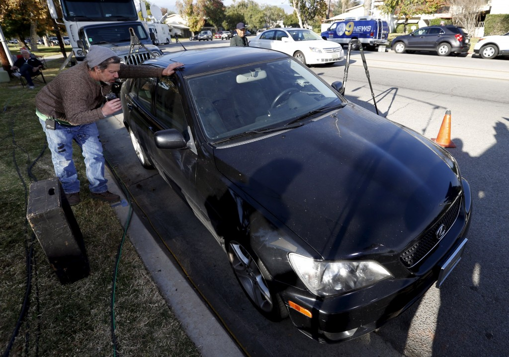 A man takes a photo of a vehicle that was searched by the FBI, which is thought to have belonged to suspects Syed Rizwan Farook and Tashfeen Malik, outside their home in Redlands, California December 4, 2015. (Mario Anzuoni/Reuters)