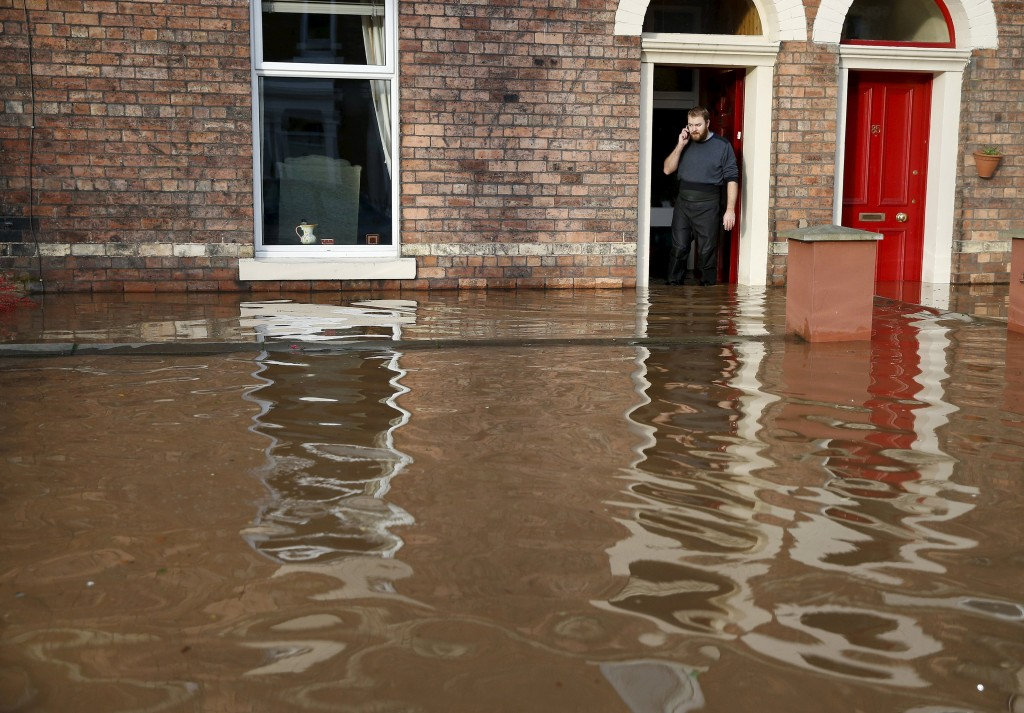 A man talks on a mobile phone as he stands in the doorway of a flooded house on a residential street in Carlisle, Britain December 6, 2015. British police have declared a major incident in northern England after prolonged heavy rain caused widespread flooding and forced emergency services to evacuate residents from their homes. REUTERS/Phil Noble
