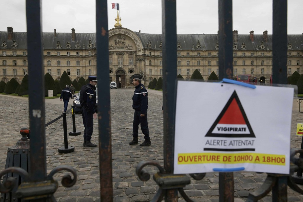 French gendarmes are seen behind the closed entrance of the Invalides monument in Paris, France, December 16, 2015. French police fired on a car that lurched towards a military museum building in Paris on Wednesday and arrested the driver, a police official said. REUTERS/Philippe Wojazer