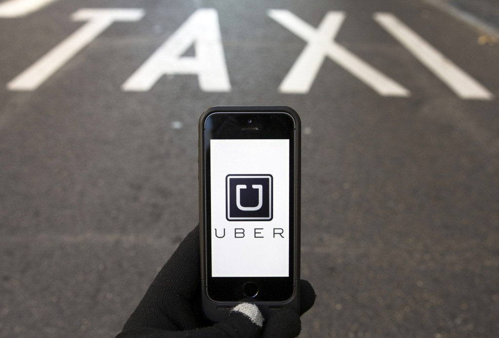 The logo of car-sharing service app Uber on a smartphone over a reserved lane for taxis in a street is seen in this file photo. (Sergio Perez/Reuters/Files)