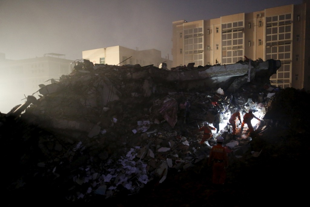 Firefighters search for survivors in the rubble of collapsed buildings after a landslide hit an industrial park in Shenzhen, Guangdong province, China, on Sunday. (Reuters/Tyrone Siu)