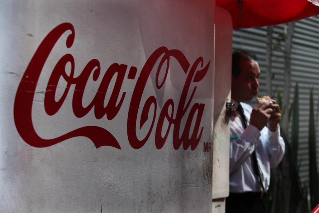 A man eats a sandwich nexto to a Coca-Cola sign in Mexico City, Dec. 2. (AP Photo/Marco Ugarte)