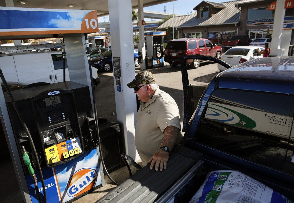 Curtis Floyd watches the gas pump while filling up his Dodge Ram pickup at Fuel City in Dallas. (Rose Baca/Dallas Morning News/TNS)