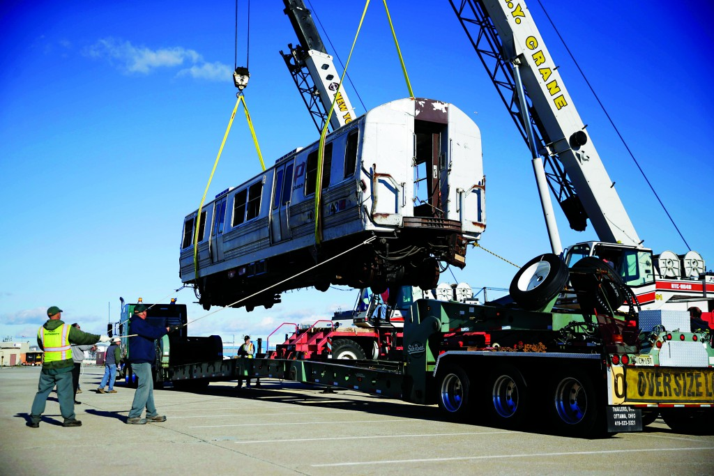A damaged carriage of a PATH train that once carried commuters from New Jersey to the World Trade Center is loaded Tuesday onto a truck in Kennedy Airport. (AP Photo/Seth Wenig)