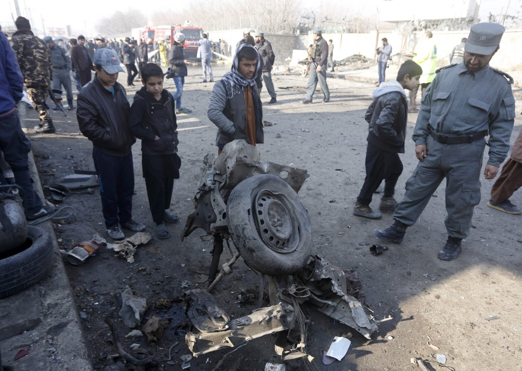 An Afghan policeman and locals look at the wreckage of a car at the site of a suicide bomb attack in Kabul, Afghanistan, December 28, 2015. A suicide bomber killed at least one person and wounded 13 in an attack on a road near Kabul airport, officials in the Afghan capital said on Monday, barely two weeks after a major Taliban assault in the city. REUTERS/Omar Sobhani