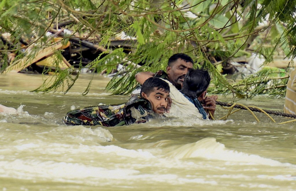Indian army soldiers rescue a man from flood waters in Chennai, India, Thursday, Dec. 3, 2015. The heaviest rainfall in more than 100 years has devastated swathes of the southern Indian state of Tamil Nadu, with thousands forced to leave their submerged homes and schools, offices and a regional airport shut for a second day Thursday.( R Senthil Kumar / Press Trust of India via AP)