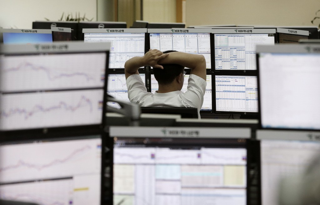 A currency trader watches monitors at the foreign exchange dealing room of the KEB Hana Bank headquarters in Seoul, South Korea, Tuesday, Sept. 1, 2015. Asian shares fell Tuesday as gloomy manufacturing data from China and weak investment figures in Japan augured further uncertainty for investors after a brutal August.(AP Photo/Ahnn Young-joon)