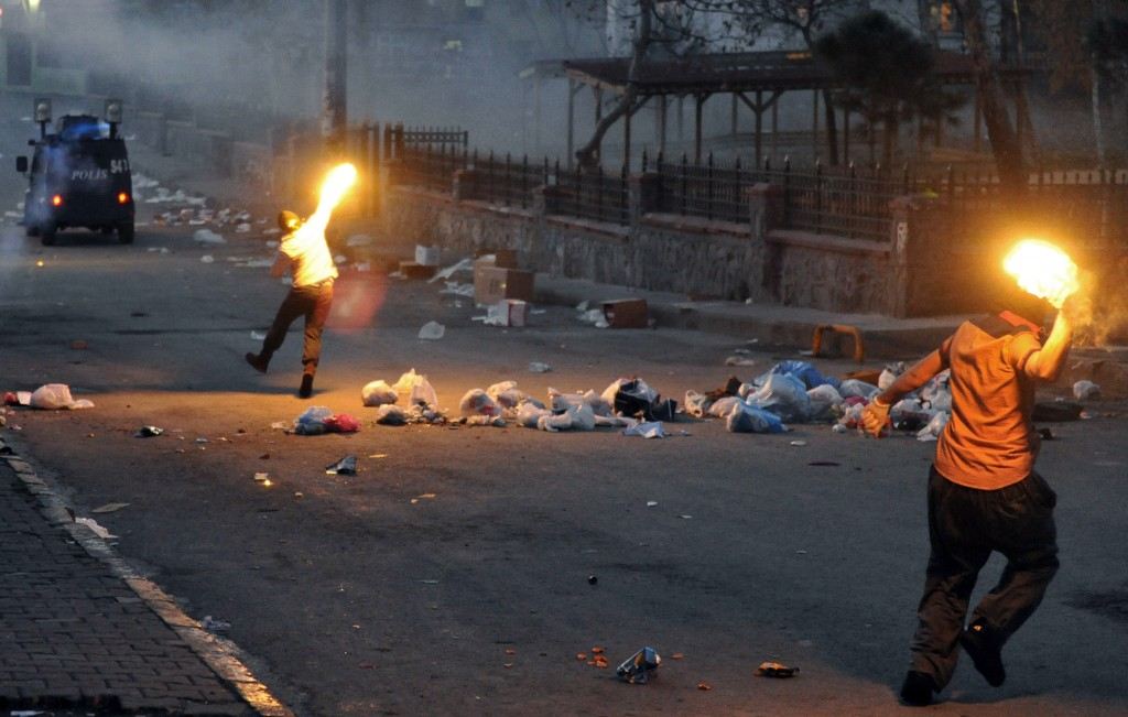 Masked men throw petrol bombs towards police who used water cannons and teargas to disperse people protesting against security operations against Kurdish rebels in southeastern Turkey, in Istanbul, Sunday, Dec. 20, 2015. Security forces have killed more than 100 Kurdish rebels in last four days in southeast Turkey, news agencies' reports say. The government imposed curfews in the mainly Kurdish towns of Cizre and Silopi as the security forces battle militants linked to the Kurdistan Workers' Party, or PKK who have moved their fight for autonomy to some towns and city neighborhoods.(AP Photo/Omer Kuscu)