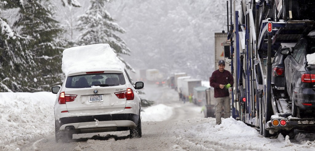 A snow-topped car drives down an on-ramp and past trucks stopped to remove chains after making the drive across Snoqualmie Pass, Wash., on Tuesday. (AP Photo/Elaine Thompson)