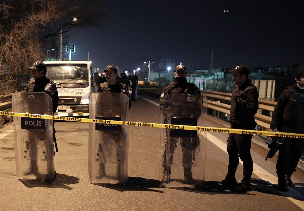 Riot police secure the area after an explosion on a highway overpass near a subway station wounds five people in Istanbul, Turkey, Tuesday. (AP Photo/Cagdas Erdogan)
