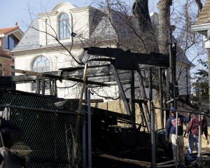 A single-family home rises above men working in the remains of a construction site that was destroyed by arson in Forest Hills, Queens, on Monday. (AP Photo/Seth Wenig)
