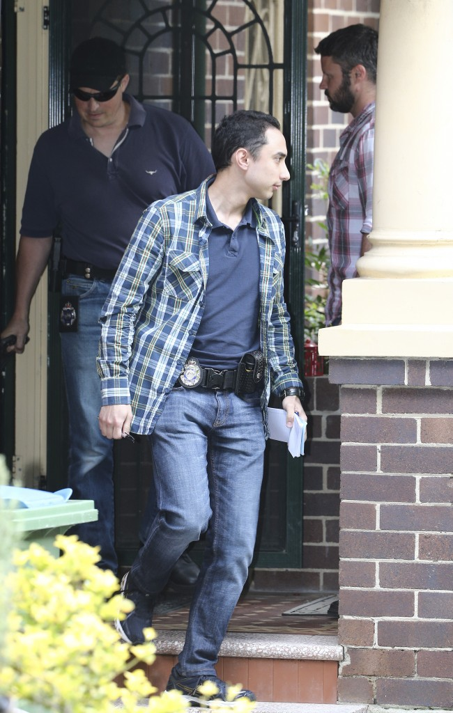 Federal police officers leave the home of a man in Sydney, Australia, on Wednesday after searching the property as part of a tax investigation. Technology news sites have alleged the man is the creator of the virtual currency Bitcoin.(AP Photo/Rob Griffith)