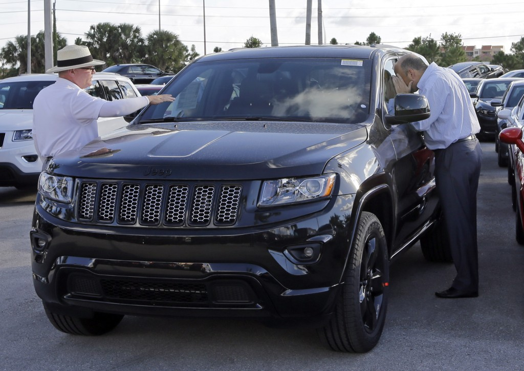 Salesman Andrew Montalvo, left, talks to a customer checking out the interior of a 2015 Grand Cherokee Limited in Doral, Fla. (AP Photo/Alan Diaz)