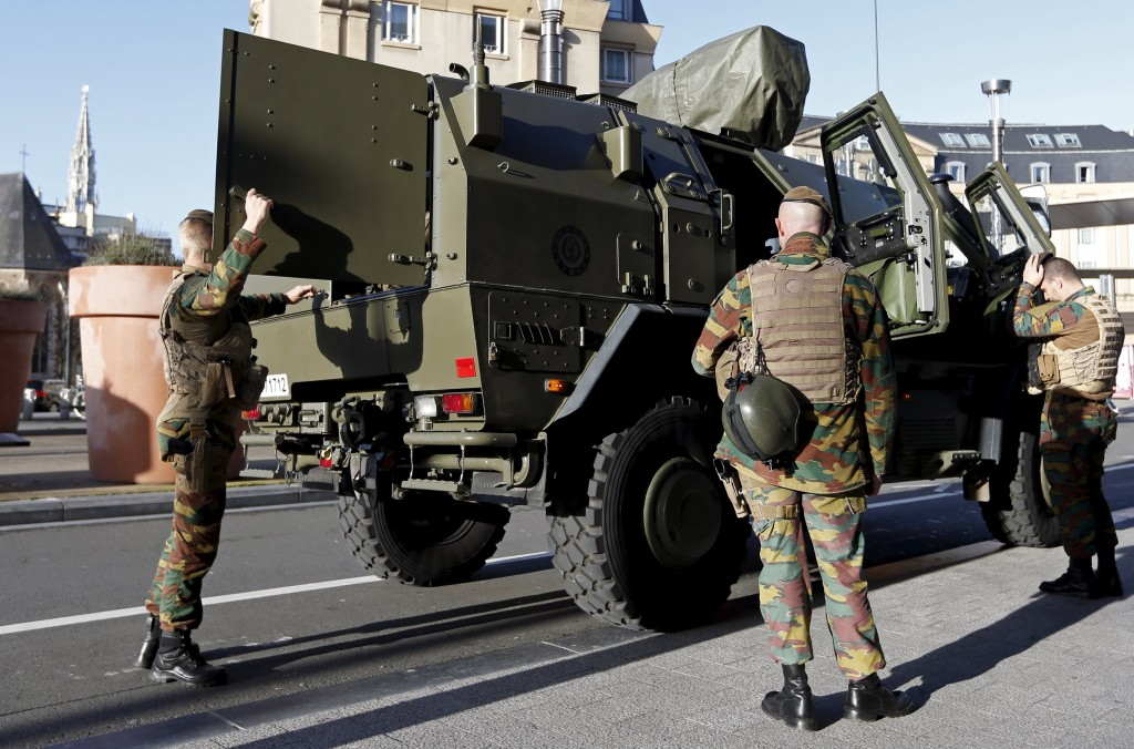 Belgian soldiers stand next to a military armoured vehicle as they patrol in central Brussels, December 31, 2015. Belgian police have detained six people during house searches in Brussels in an investigation into a plot to carry out an attack in the city on New Year's Eve, prosecutors said on Thursday.    REUTERS/Francois Lenoir