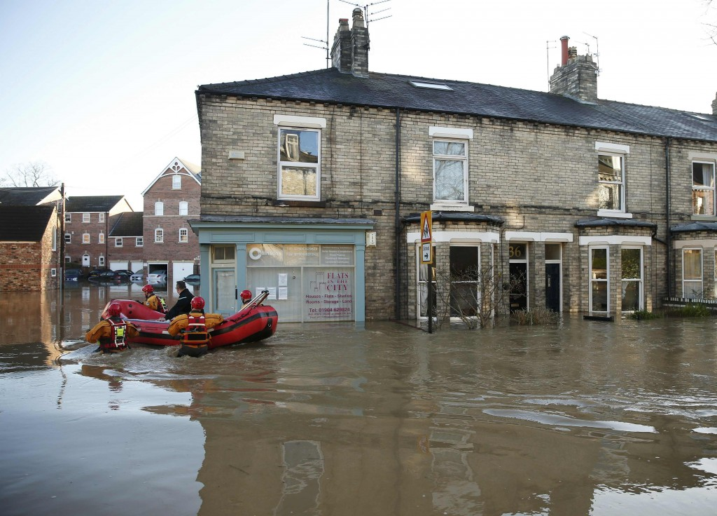 Emergency services help a resident return to his home in a flooded street in York, northern England, December 27, 2015. REUTERS/Phil Noble