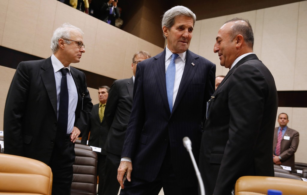 U.S. Secretary of State John Kerry, centre, greets Turkish Foreign Minister Mevlut Cavusoglu, right, as they arrive for a NATO ministerial meeting on Resolute Support operations in Afghanistan, at NATO Headquarters in Brussels Tuesday, Dec. 1, 2015. (Jonathan Ernst/Pool Photo via AP)