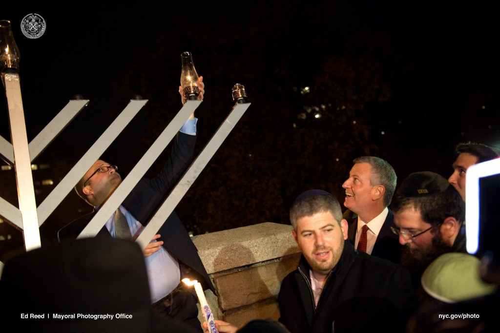 Mayor Bill de Blasio on Monday joins community members and residents for the re-lighting of the menorah in Carl Schurz Park, which was vandalized the night before.