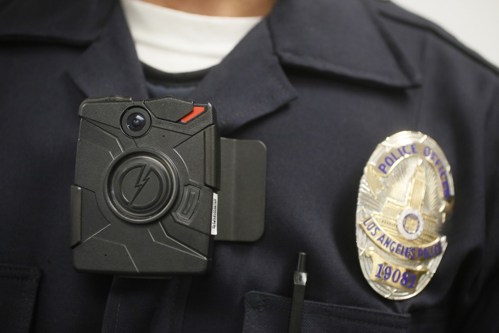 FILE - In this Jan. 15, 2014 file photo a Los Angeles Police officer wears an on-body camera during a demonstration in Los Angeles. During the last three months of 2014, Customs and Border Protection tested cameras in simulated environments including the Border Patrol training academy in Artesia, New Mexico. From January to May, it expanded testing to 90 agents and officers who volunteered across the country to use the cameras on the jobs. The yearlong review cited cost and a host of other reasons to hold off, according to two people familiar with the findings who spoke on condition of anonymity because the findings have not been made public. (AP Photo/Damian Dovarganes, File)
