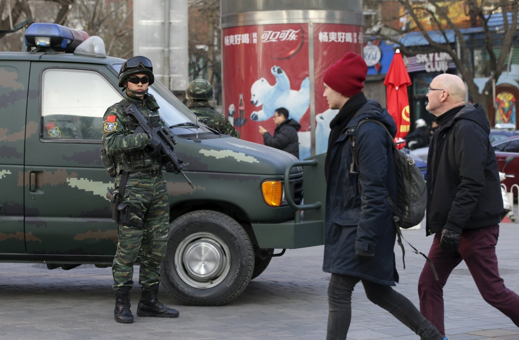 Pedestrians walk by as armed policemen of the Snow Leopard Commando Unit (L) stand guard near a police van at the Sanlitun area, a fashionable location for shopping and dining, in Beijing, China, December 24, 2015. U.S. Embassy in China issued a notice on its website on Thursday warning people about possible threads against westerners in this area on or around Christmas Day. REUTERS/Jason Lee