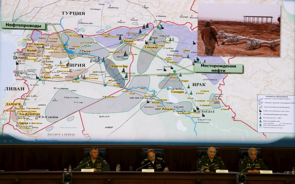 Russian Defence Ministry officials sit under a display showing the Turkish-Syrian border during a briefing in Moscow, Russia, December 2, 2015. Russia's defence ministry said on Wednesday it had proof that Turkish President Tayyip Erdogan and his family were benefiting from the illegal smuggling of oil from Islamic State-held territory in Syria and Iraq. REUTERS/Sergei Karpukhin