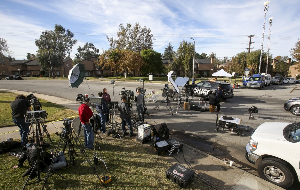 Media wait at the police line near a home in connection to the San Bernardino shootings, on Thursday, in Redlands, Calif. (AP Photo/Ringo H.W. Chiu)