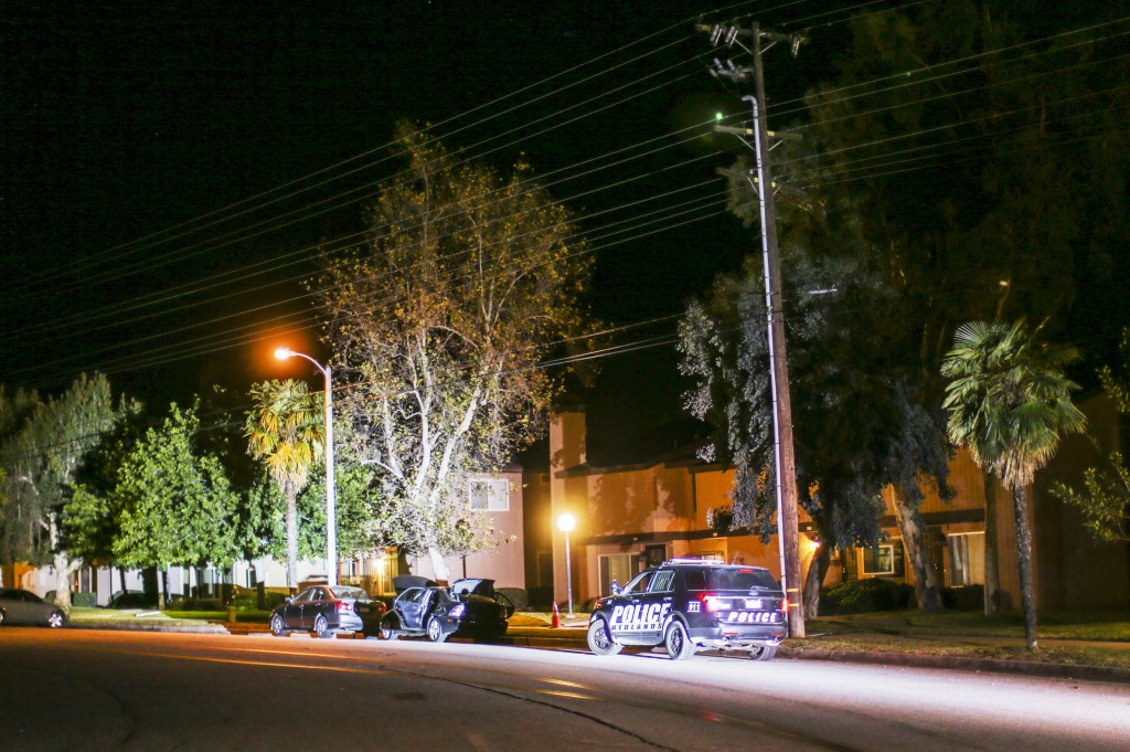 A police car parks in front of a home being investigated by authorities, on Thursday, Dec. 3, 2015, in Redlands, Calif. A heavily armed man and woman opened fire Wednesday on a holiday banquet for his co-workers, killing multiple people and seriously wounding others in a precision assault, authorities said. Hours later, they died in a shootout with police. (AP Photo/Ringo H.W. Chiu)