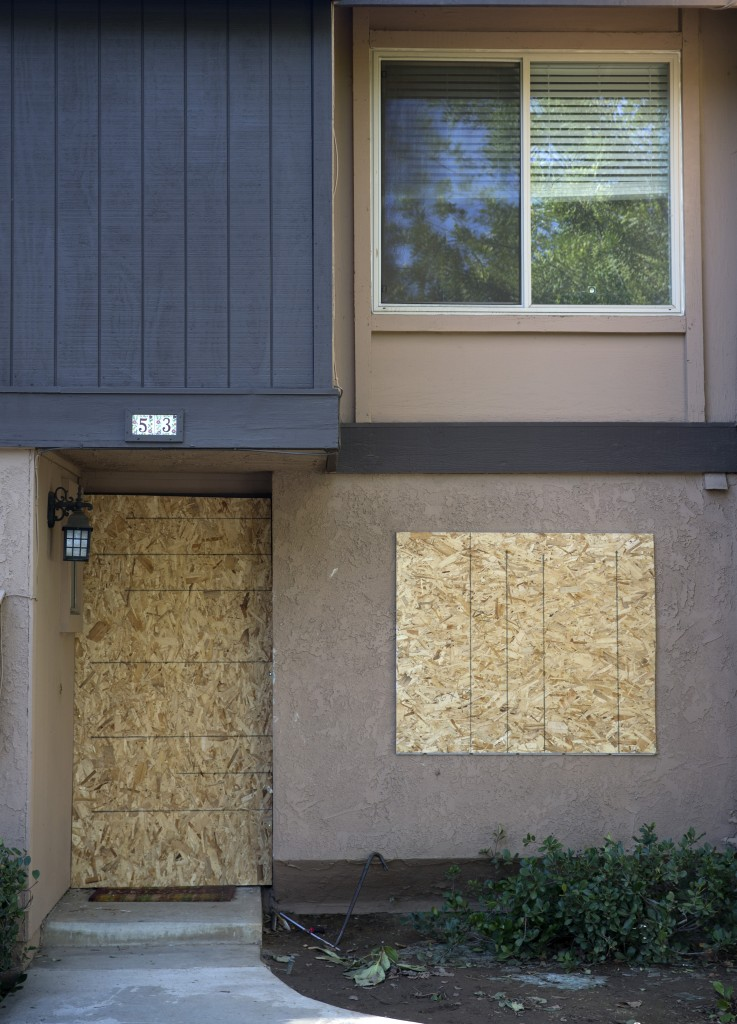 The townhouse rented by San Bernardino shooting rampage suspects Syed Farook and his wife, Tashfeen Malik, is boarded up, Saturday, Dec. 5, 2015, in Redlands, Calif. The Pakistani woman who joined her U.S.-born husband in killing multiple people in a commando-style assault on his co-workers is at the center of a massive FBI terrorism investigation, yet she remains shrouded in mystery. (AP Photo/Jae C. Hong)