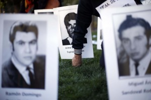 In this Sept. 11, 2015 photo, a man places a photo of a disappeared person outside La Moneda presidential palace in Santiago, Chile, on the anniversary of Chile's coup.  (AP Photo/Luis Hidalgo, File)