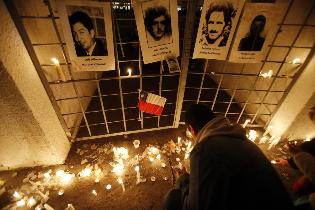 In this Sept. 11, 2015 photo, a man lights a candle at the National Stadium, which served as a detention center in the early years of the military dictatorship, during a vigil marking the 42nd anniversary of the military coup that ousted the late President Salvador Allende, in Santiago, Chile. (AP Photo/Luis Hidalgo, File)