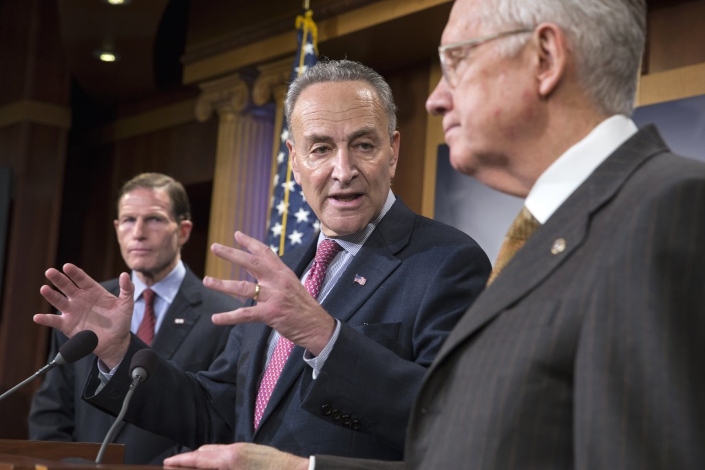 Senator Charles Schumer, D-N.Y. (C), flanked by Senator Richard Blumenthal, D-Conn. (L) and Senate Minority Leader Harry Reid of Nev. (R), during a news conference on Capitol Hill in Washington, Nov. 19. (AP Photo/J. Scott Applewhite)
