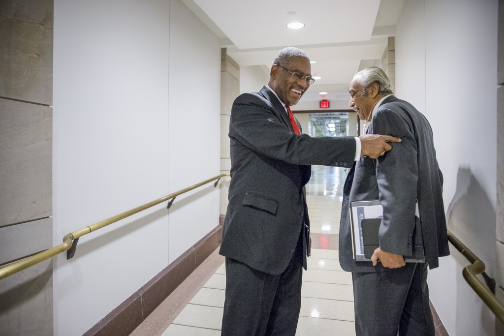 Rep. Gregory W. Meeks, D-N.Y., center, smiles as he has a friendly exchange with Rep. Charlie Rangel, D-N.Y., right, as the two New York lawmakers pass in a basement corridor on Capitol Hill in Washington, Wednesday, Nov. 18, 2015. (AP Photo/J. Scott Applewhite)